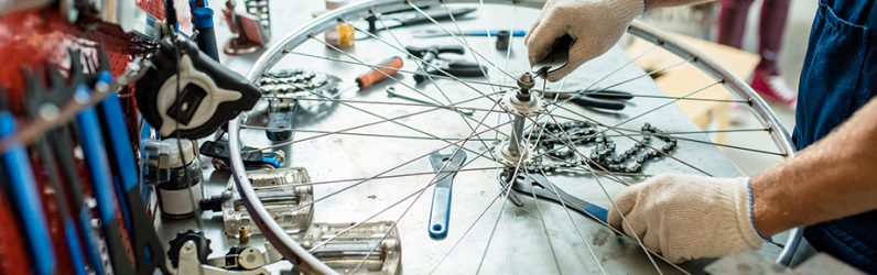 Gloved hands of repairing master tightening bolts on wheel by workplace